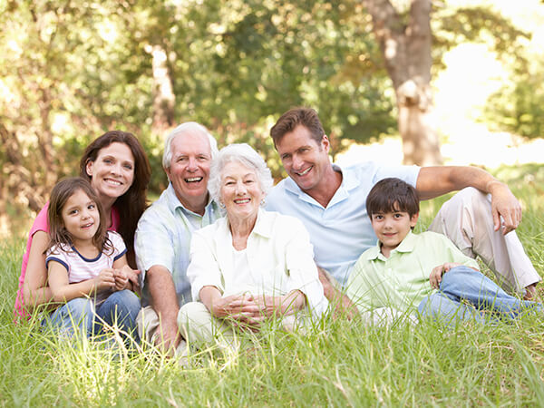 A family of parents and two grandparents sitting on the grass in a park