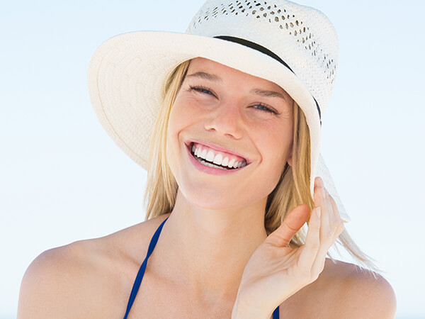 A young woman smiling at the beach while wearing a hat