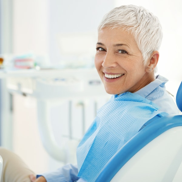 Mature woman with grey hair and blue top looking back at her restorative dentist