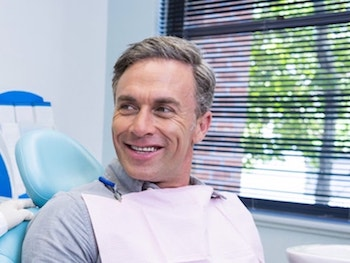 Mature man sitting in a dental chair talking to the dentist at his right about our services