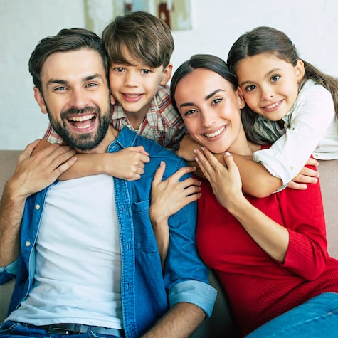 A family with two children laughing and hugging their parents
