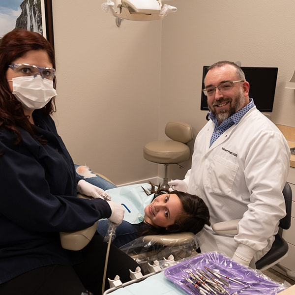 Our Monroe specialist and one of his dental assistants next to a young woman who is lying in the dentist's chair smiling