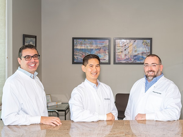 Our three dentists in Monroe WA, reclining at our front office and smiling