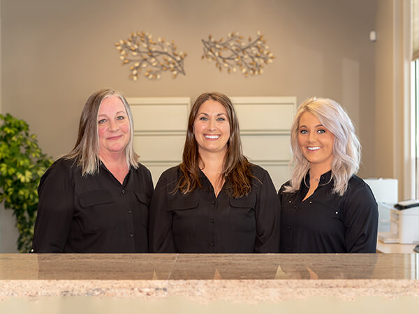 Our three dental assistants standing behind the front desk and smiling